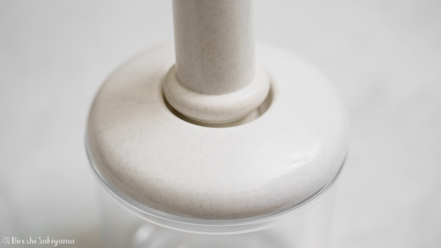 加藤産業 真空保存庫の容器にポンプを当てて脱気する様子